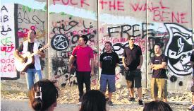 Els músics de la brigada davant del mur que encercla Cisjordània